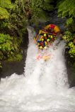 Les touristes plongent en bas d'une cascade sur une eau blanche transportant le cours par radeau aux cascades de Kaituna dans Rot photographie stock libre de droits
