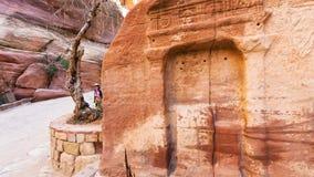 Les touristes près du soulagement en pierre en Al Siq passent à PETRA Photographie stock libre de droits