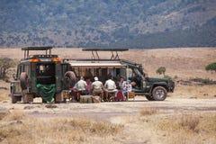 Les touristes prennent le déjeuner près de leur voiture de safari photographie stock libre de droits