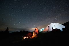 Les touristes s'approchent du feu de camp et de la tente sous le ciel étoilé de nuit Photographie stock libre de droits