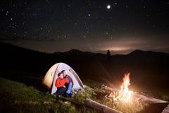 Les touristes s'approchent du feu de camp et de la tente sous le ciel étoilé de nuit Photos stock