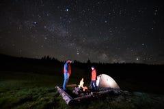 Les touristes s'approchent du feu de camp et de la tente sous le ciel étoilé de nuit Photos libres de droits