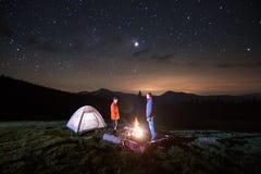 Les touristes s'approchent du feu de camp et de la tente sous le ciel étoilé de nuit Image libre de droits