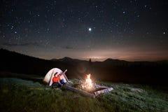 Les touristes s'approchent du feu de camp et de la tente sous le ciel étoilé de nuit Image stock