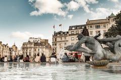 Les touristes s'asseyent par la fontaine dans Trafalgar Square Photographie stock