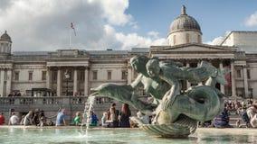 Les touristes s'asseyent par la fontaine dans Trafalgar Square avec la statue et le National Gallery de sirène Photos libres de droits