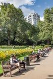 Les touristes s'asseyent sur le banc dans le jardin sur le remblai, au nord de la Tamise Photo libre de droits