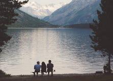 Les touristes s'asseyent sur un banc sur le rivage du lac alpin Image stock