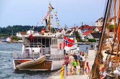 Les touristes sur le bord de mer voient les bateaux colorés images stock