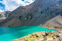 Les touristes sur le rivage d'une aile du nez-Kul de lac de montagne, Kirghizistan Photographie stock libre de droits