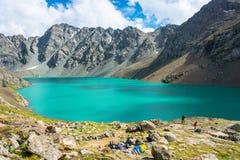 Les touristes sur le rivage d'une aile du nez-Kul de lac de montagne, Kirghizistan Photos libres de droits