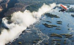 Les touristes volent au-dessus de Victoria Falls sur les tricycles Image stock