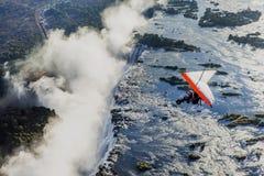 Les touristes volent au-dessus de Victoria Falls sur les tricycles Image libre de droits