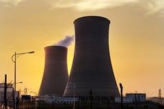 Les tours de refroidissement des centrales nucléaires dans le coucher du soleil Photographie stock