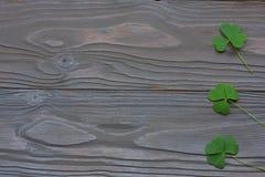 Les trèfles de plan rapproché part sur la vue supérieure de fond en bois foncé avec l'espace de copie Photographie stock