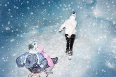 Les traîneaux avec des enfants joints ont tiré sur la neige par la femme pendant l'hiver images stock