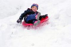 Les traîneaux riants d'enfant avalent une colline image stock