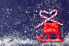 Les traîneaux rouges de Noël portent le boîte-cadeau, lucette rayée photos libres de droits