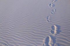 Les traces des personnes sur le sable blanc sont parties le temps clair chaud Image libre de droits