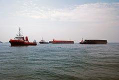 Les tractions subites et barges dedans l'ancrage de Singapour. photo stock