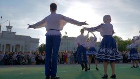 Les traditions ethniques, jeunesse dans des costumes nationaux dansent la danse folklorique dans le secteur de ville devant publi banque de vidéos