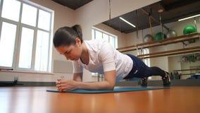 Les trains de fille dans le centre de fitness Fait une planche d'exercice 4K MOIS lent banque de vidéos