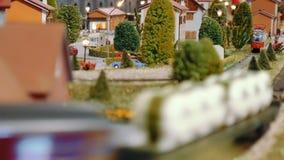 Les trains modèles transitent et un tram part sur un diorama banque de vidéos