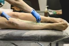 Les traitements cosmétiques pour l'épilation sur des jambes se ferment  Photo libre de droits