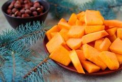 Les tranches découpées en tranches de potiron pour Noël durcissent avec les branches impeccables Photos stock