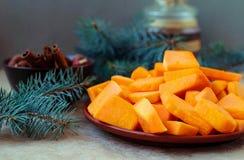 Les tranches découpées en tranches de potiron pour Noël durcissent avec les branches impeccables Images libres de droits