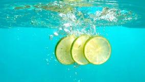 Les tranches de citron tombent dans l'eau bleue avec des bulles en dessus de table sous-marin de tir de mouvement lent banque de vidéos