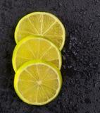 Les tranches de Lima fraîches avec de l'eau chute sur le noir Photo libre de droits