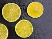 Les tranches de Lima fraîches avec de l'eau chute sur le noir Photo stock