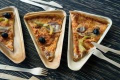 Les tranches de pizza est d'un plat en bois Image stock