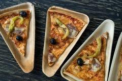 Les tranches de pizza est d'un plat en bois Photo libre de droits