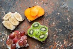 Les tranches de variété de pain de seigle grillent avec des fruits Kaki de banane, Images stock