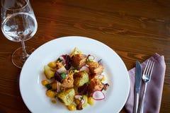 Les tranches et les betteraves cuites au four de pomme de terre avec le lard de légumes et de rôti de porc sur la table en bois f Photos stock