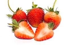 Les tranches et une fraise rouge de demi groupe sur la fraise poussent des feuilles Image libre de droits