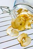 Les tranches sèches de pomme sur la grille et le verre en métal cognent Images libres de droits