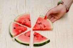 Les tranches triangulaires de pastèque se trouvant sur un cercle une main femelle prend une tranche, fond en bois clair Photo stock