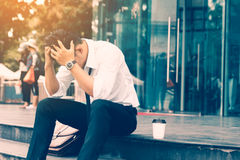 Les travailleurs équipent le mal de tête se reposant devant la société au sujet de son W photographie stock