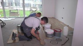 Les travailleurs amateurs étendent le panneau de parquet sur le plancher près des dalles d'hexagone clips vidéos