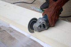 Les travailleurs asiatiques employant la circulaire électrique ont vu couper le bois artificiel Photo stock