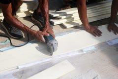 Les travailleurs asiatiques employant la circulaire électrique ont vu couper le bois artificiel Photo libre de droits