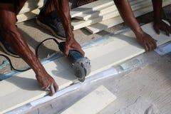 Les travailleurs asiatiques employant la circulaire électrique ont vu couper le bois artificiel Image libre de droits