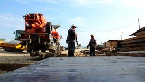 Les travailleurs au chantier de construction se tiennent à la grue de camion en discutant des plans de travail clips vidéos