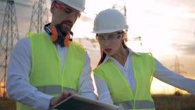 Les travailleurs d'électricien discutent le plan de construction sur un fond de coucher du soleil, se ferment  banque de vidéos