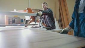 Les travailleurs d'hommes à l'usine coupent le fragment en bois sur la scie électrique à l'industrie du meuble photographie stock
