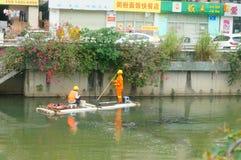 Les travailleurs d'hygiène nettoient des déchets de rivière photographie stock libre de droits