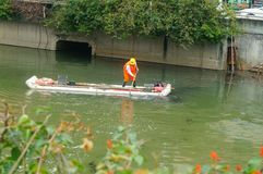 Les travailleurs d'hygiène nettoient des déchets de rivière images stock